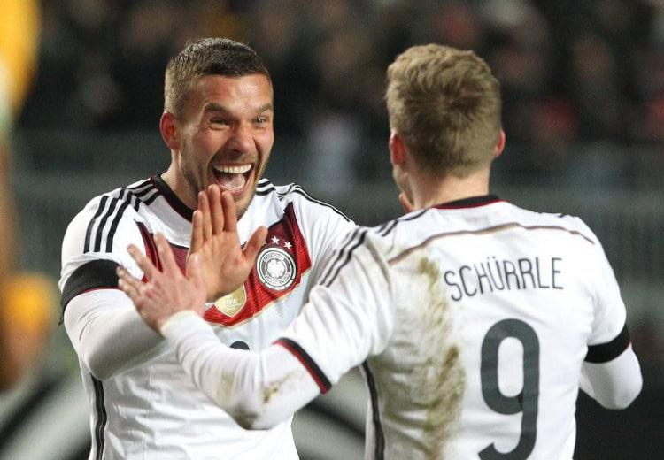 Lukas Podolski (L) bejubelt sein Tor zum 2:2 mit Andre Schuerrle gegen Australien in Kaiserslautern, am 25.März 2015. AFP PHOTO / DANIEL ROLAND