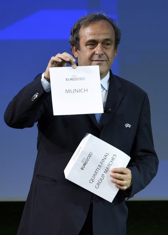 UEFA President Michel Platini hält die Karte für München hoch, in der drei Gruppenspiele und ein Viertelfinale stattfinden werden. ( AFP PHOTO / FABRICE COFFRINI )