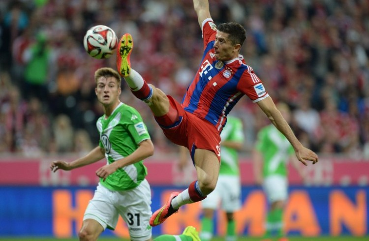 Bayern Munich's Polish striker Robert Lewandowski (R) and Wolfsburg's defender Robin Knoche (L) vie for the ball during the German first division Bundesliga football match FC Bayern Munich vs VfL Wolfsburg at the Allianz Arena in Munich, southern Germany on August 22, 2014. AFP PHOTO / CHRISTOF STACHE DFL RULES TO LIMIT THE ONLINE USAGE DURING MATCH TIME TO 15 PICTURES PER MATCH. IMAGE SEQUENCES TO SIMULATE VIDEO IS NOT ALLOWED AT ANY TIME. FOR FURTHER QUERIES PLEASE CONTACT DFL DIRECTLY AT + 49 69 650050.