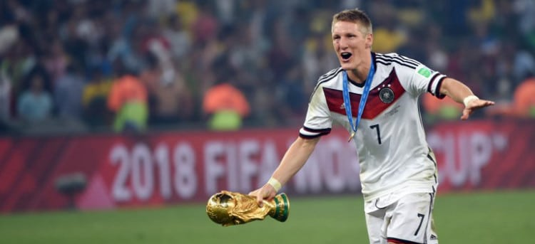Germany's midfielder Bastian Schweinsteiger runs with the World Cup trophy as he celebrates with teammates after winning the 2014 FIFA World Cup final football match between Germany and Argentina 1-0 following extra-time at the Maracana Stadium in Rio de Janeiro, Brazil, on July 13, 2014. AFP PHOTO / PATRIK STOLLARZ