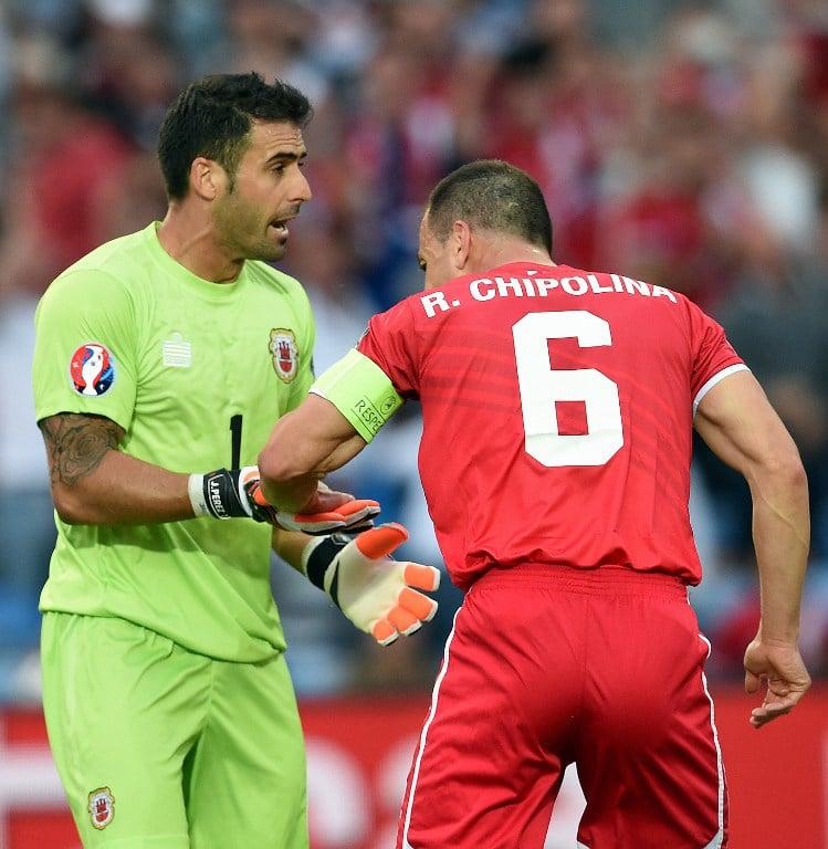 Gibraltar's Abwehrspieler Roy Chipolina gratuliert Torwart Jordan Perez (L) zum gehaltenen Elfmeter gegen Bastian Schweinsteiger beim Vorrundenspiel gegen Deutshcland in Faro am 13.Juni 2015. AFP PHOTO/ FRANCISCO LEONG