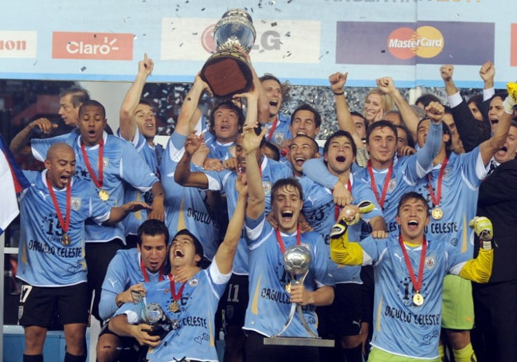 Uruguays's Kapitän Diego Lugano (C) stemmt den Pokal der Copa America 2011 in die Höhe - man gewinnt gegen Paraguay mit 3:0. AFP PHOTO / ANTONIO SCORZA