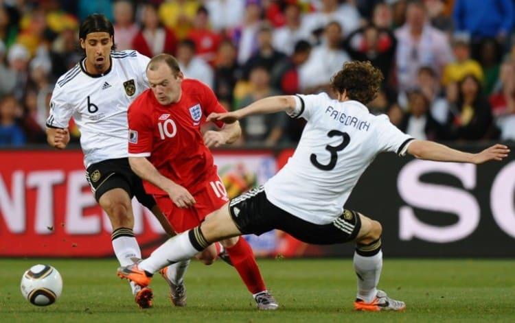 Arne Friedrich (R) und Sami Khedira (R) gegen Wayne Rooney (C) bei der WM 2010 in Südafrika am 27.Juni 2010 im Free State stadium in Mangaung/Bloemfontein. AFP PHOTO / PAUL ELLIS
