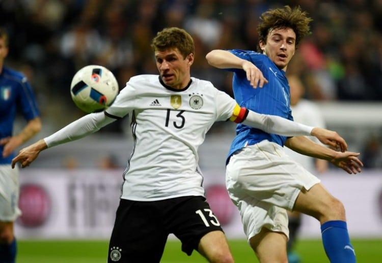 Thomas Müller und Italiens Matteo Darmian am 29.März 2016. / AFP / PATRIK STOLLARZ