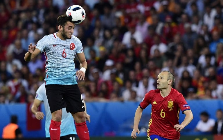 Turkey's midfielder Hakan Calhanoglu (L) heads the ball as Spain's midfielder Andres Iniesta runs past during the Euro 2016 group D football match between Spain and Turkey at the Allianz Riviera stadium in Nice on June 17, 2016. / AFP PHOTO / TOBIAS SCHWARZ