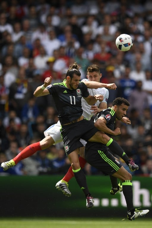 Wales' forward Gareth Bale heads the ball next to Wales' forward Hal Robson-Kanu and England's defender Gary Cahill during the Euro 2016 group B football match between England and Wales at the Bollaert-Delelis stadium in Lens on June 16, 2016. / AFP PHOTO / MARTIN BUREAU