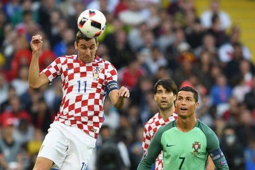 Kroatiens Darijo Srna beim Kopfball,  Portugal's Stürmer Cristiano Ronaldo schaut zu - der neue Spielball der EM Fracas. / AFP PHOTO / FRANCISCO LEONG