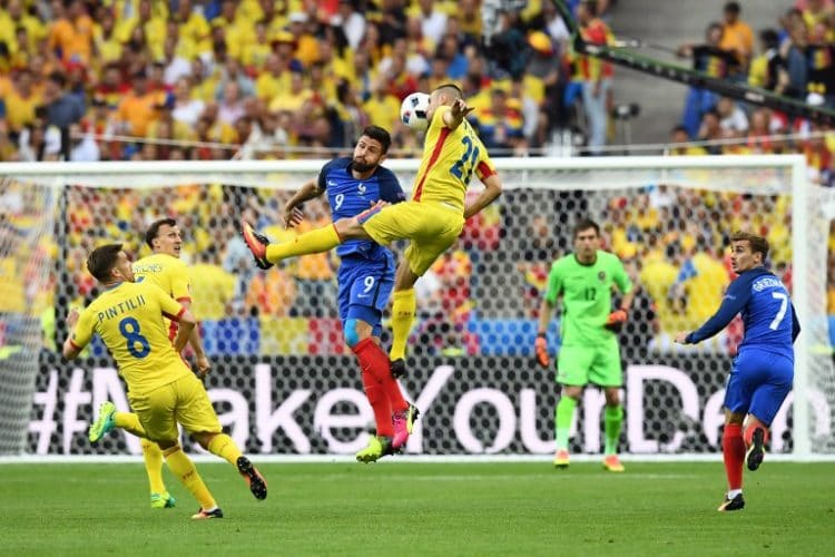 Olivier Giroud und Rumäniens Dragos Grigori (im Luftkampf. / AFP PHOTO / FRANCK FI