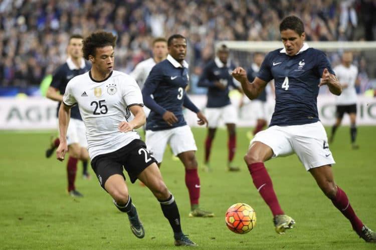 Leroy Sane (L) gegen den Franzosen Raphael Varane beim Testspiel gegen Frankreich am 13.11.2015 in Paris. AFP PHOTO / MIGUEL MEDINA / AFP / MIGUEL MEDINA