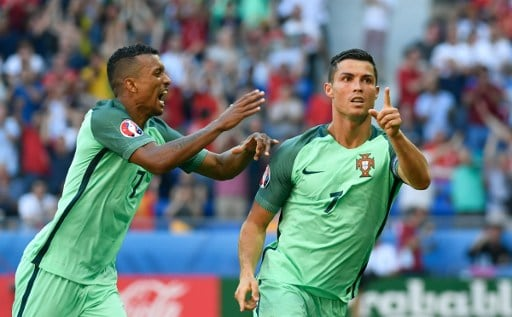 Portugal's forward Cristiano Ronaldo (R) celebrates after scoring a goal during the Euro 2016 group F football match between Hungary and Portugal at the Parc Olympique Lyonnais stadium in Decines-Charpieu, near Lyon, on June 22, 2016. / AFP PHOTO / PHILIPPE DESMAZES