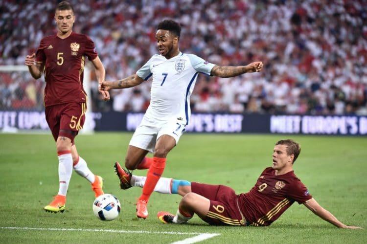 England's Raheem Sterling (C) gegen Alexander Kokorin (R) und Roman Neustaedter. / AFP PHOTO / BERTRAND LANGLOIS