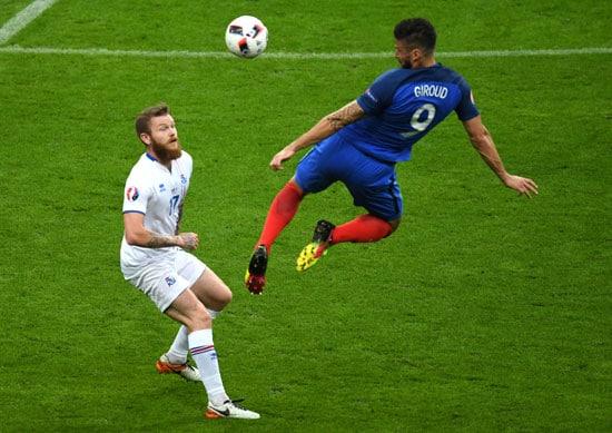 Oliver Giroud erzielt das 1:0 gegen Island, der isländische Kapitän Aron Gunnarsson kann nur zusehen und staunen (Francisco LEONG / AFP)