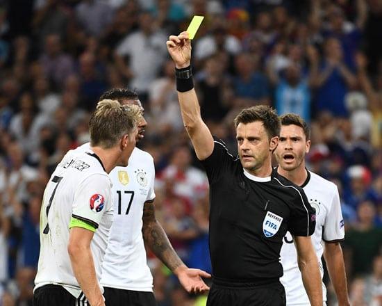 Bastian Schweinsteiger bekommt nach Handspiel im Elfer die gelbe Karte von Nicola Rizzoli - Elfmeter und somit das 1:0 für Frankreich durch Antoine Griezmann. / AFP PHOTO / ANNE-CHRISTINE POUJOULAT