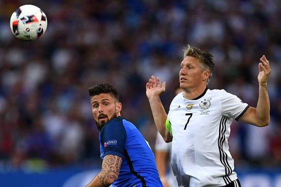 Olivier Giroud gegen Bastian Schweinsteiger / AFP PHOTO / PATRIK STOLLARZ