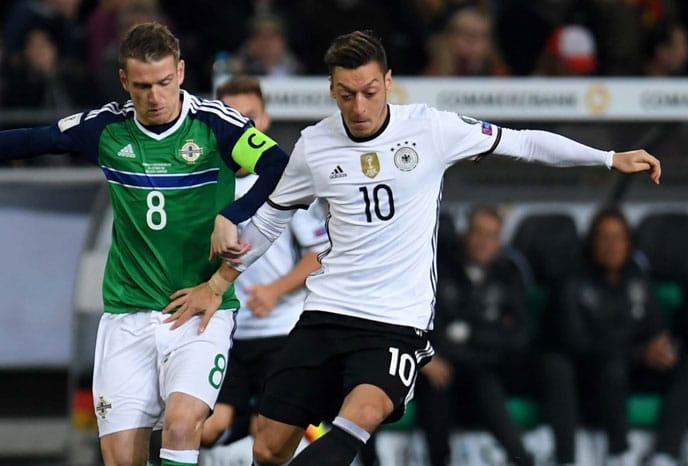 Mesut Özil (R) mit seiner neuen Rückennummer gegen Nordirlands Steven Davis beim WC 2018 Qualispiel in Hannover am 11.Oktober 2016. / AFP PHOTO / PATRIK STOLLARZ