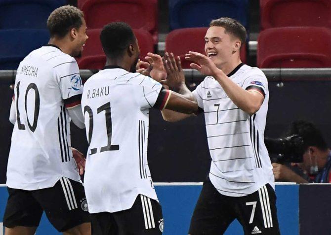 Deutschlands Stürmer Florian Wirtz (R) feiert mit seinen Teamkollegen Lukas Nmecha und Verteidiger Ridle Baku, die während des UEFA-U21-Fußball-Halbfinalspiels zwischen den Niederlanden und Deutschland in Szekesfehervar am 3. Juni 2021 das zweite Tor für sein Team erzielen. Attila KISBENEDEK / AFP